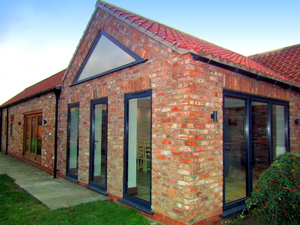 Converted barn with glass doors and full length windows