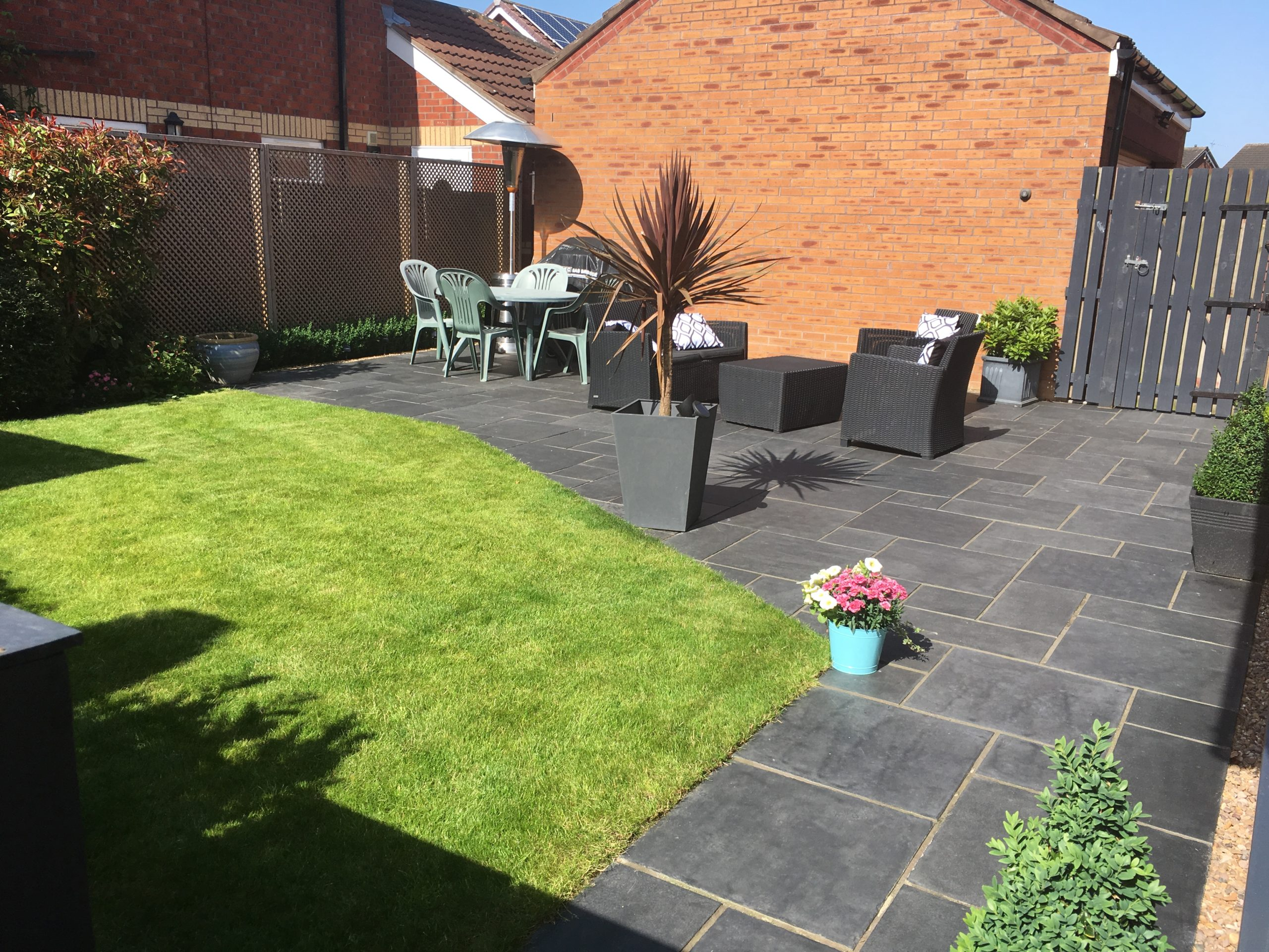 Lawn furniture and garden in front of a single storey extension